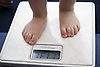 Toddler standing on the bathroom scales,
