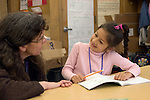 Oakland CA Latina 1st grader talking to teacher about her work
