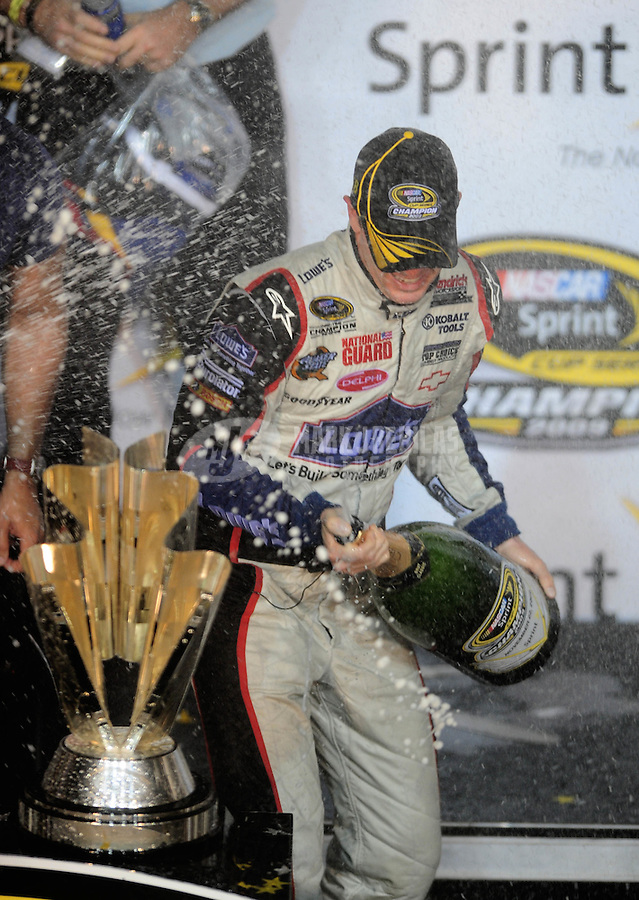 Nov. 22, 2009; Homestead, FL, USA; NASCAR Sprint Cup Series driver Jimmie Johnson celebrates with champagne after winning the 2009 Sprint Cup championship following the Ford 400 at Homestead Miami Speedway. The championship is the fourth consecutive for Johnson. Mandatory Credit: Mark J. Rebilas-