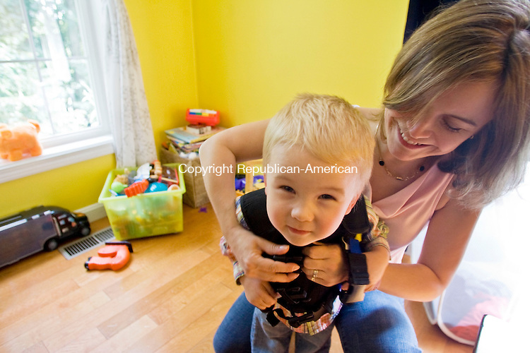SOUTHBURY, CT - 15 SEPTEMBER 2009 -091509JT03-<br /> Lauren Brenneman clips her son Isaac, 2, into his vest at their Southbury home on Tuesday. The two have cystic fibrosis, an inherited disease that affects the lungs and digestive system, and the vests are used to clear the air passage of the lungs . The two wear the vest at least twice a day for at least 30 minutes at a time. Lauren is helping organize the 10th annual Evening of Comedy of Hope to benefit the Cystic Fibrosis Foundation on Saturday, Sept. 26 at the Heritage Hotel in Southbury. For more information, contact Cassandra Davis at the Cystic Fibrosis Foundation at 860-257-6907.<br /> Josalee Thrift Republican-American