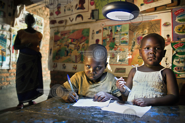Viola Candiru (5) and Iren Tayisi (4) write on pieces of paper under the light of a Philips Solar Light System in the village of Offaka.