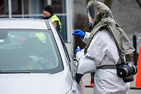A medical worker wearing a protective hood uses a swab to take a sample from a patient as part of COVID-19 drive-through testing in a parking lot near the Cambridge Health Alliance Women's Health Hospital in Somerville, Massachusetts, on Mon., March 23, 2020. Patients could make appointments to drive through the parking lot to get tested for the virus during the ongoing Coronavirus (COVID-19) global pandemic. This location is one of a handful of such testing facilities that have opened in the Boston area in the past week.