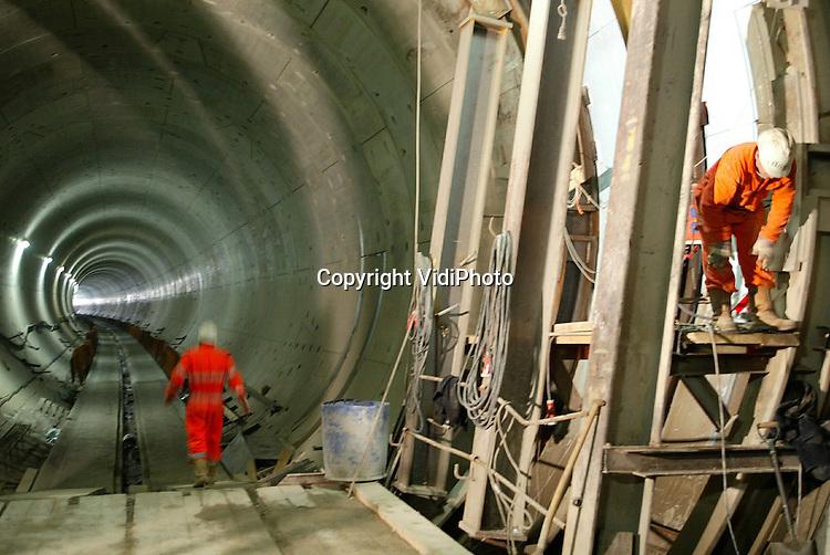 Foto: VidiPhoto..ANGEREN - Werknemers van de aannemerscombinatie Comol Tunnelbouw zijn bezig met het aanleggen van een dwarsverbinding tussen de twee buizen voor de spoortunnel onder het Pannerdensch Kanaal. In totaal komen er op de 2680 meter lange route twee vluchtroutes voor machinisten in geval van calamiteiten. De werkzaamheden zijn het tweede kwartaal van 2004 gereed, een half jaar eerder dan gepland. De bouwers krijgen binnenkort een vermelding in het Guiness Book of Records omdat het hier gaat om de snelst geboorde tunnel ooit van deze omvang. Bijzonder is ook dat de aanneemsom van 160 miljoen euro naar verwachting niet overschreden zal worden.