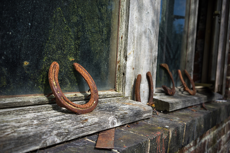 Old rusty horseshoes on a wooden window sill