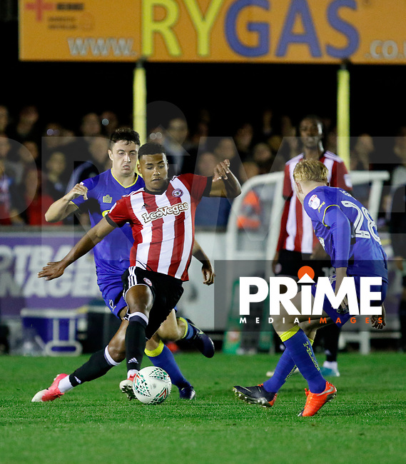 Brentford's Ollie Watkins holds off AFC Wimbledon's Anthony Hartigan during the Carabao Cup match between AFC Wimbledon and Brentford at the Cherry Red Records Stadium, Kingston, England on 8 August 2017. Photo by Carlton Myrie.