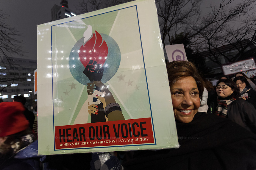 A woman holds a sign asking for Democrats' voices to be heard at a protest march by members of the Democratic Party Abroad organisation to mark the inauguration of President Donald Trump, Tokyo, Japan. Friday January 20th 2017 Around 400 people took apart in the march, which started in Hibiya Park at 6:30pm and finished in Roppongi just before 8pm, to honour the service given by President Obama and to protest against the illiberal policies expected of the new administration of President  Trump.