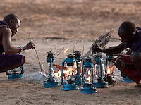 Maasai tribesman lighting Hurrican Lamps at an Eco Tourism Campsite. Near Amboseli National Park, Rift Valley Province, Kenya
