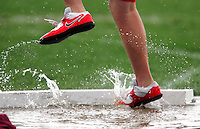 Water flies under an athlete's feet during the Boy's high school shot put April 25, 2008 at the Drake Relays in Des Moines, Iowa.  Heavy overnight rains flooded the throwing platform.