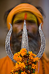 A Sadhu holds a trident adorned with marigold blossoms. Sadhus highly revere the marigold's color: orange is the color of fire, and flame is the great purifier that dispels darkness and radiates light.