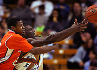 UCLA Bruins Alfred Aboya reaches for a loose ball against Sam Houston State player Shamir McDaniel in NCAA basketball 1st half action at Pauley Pavilion, December 19, 2006
