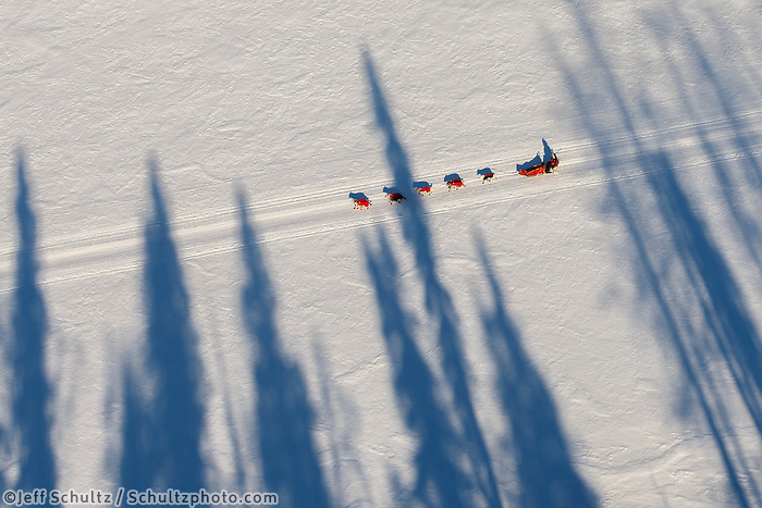 A musher and his dog team travel along the Yukon River from Ruby toward Galena on Friday, March 7, during the Iditarod Sled Dog Race 2014.<br /> <br /> PHOTO (c) BY JEFF SCHULTZ/IditarodPhotos.com -- REPRODUCTION PROHIBITED WITHOUT PERMISSION