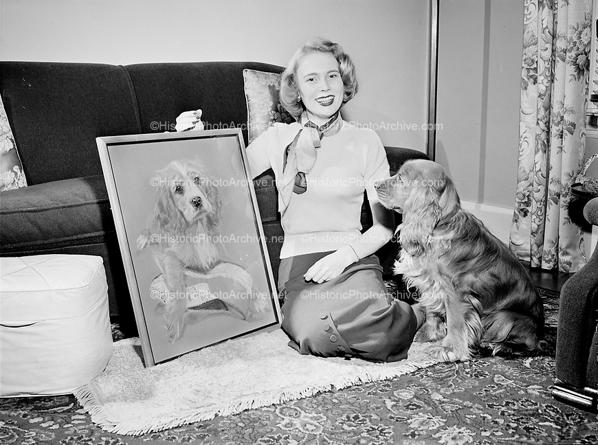 7621Woman posed with portrait of dog, with same dog sitting next to her. Models Guild. March 1949.