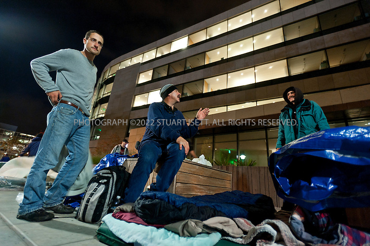 10/12/2011--Seattle, WA, USA..Homeless in Seattle, organized by SHARE (Seattle Housing and Resource Effort), camp outside the Bill and Melinda Gates Foundation in Seattle, WASH. SHARE runs 15 shelters in Seattle and says cuts in government funding have forced it to close the shelters and put 300 people onto the street. The 'sleepout' at the Gates Foundation started on Monday, Oct. 10th, with about 50 homeless camping out with blankets and tarps; SHARE organizers have asked the Gates Foundation for funds to support its local efforts to fight homelessness and reopen the closed shelters...HERE: Wade Graham, 49 (center with moustache), homeless since January, 2011, sets up his bed outside the Gates Foundation. On the left is Austin Baker, 24, originally from Arizona and homeless for 2 years...©2011 Stuart Isett. All rights reserved.