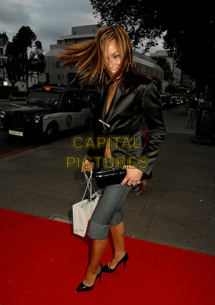 TARA PALMER TOMKINSON.The In Style 5th Birthday party at Victoria and Albert Museum, London, UK. .June 19, 2006.Ref: SW.full lengthjeans denim rolled up windy hair goody bag black satin jacket clutch purse.www.capitalpictures.com.sales@capitalpictures.com.©Capital Pictures.