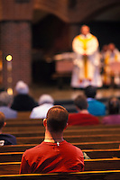 Young man listening to a priest during mass