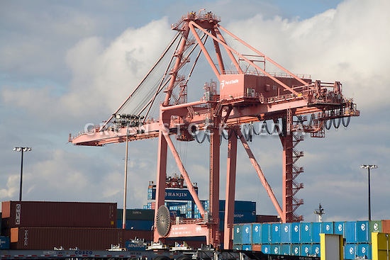 Shipping crane loading cargo containers at Port of Seattle. Seattle, Washington, USA