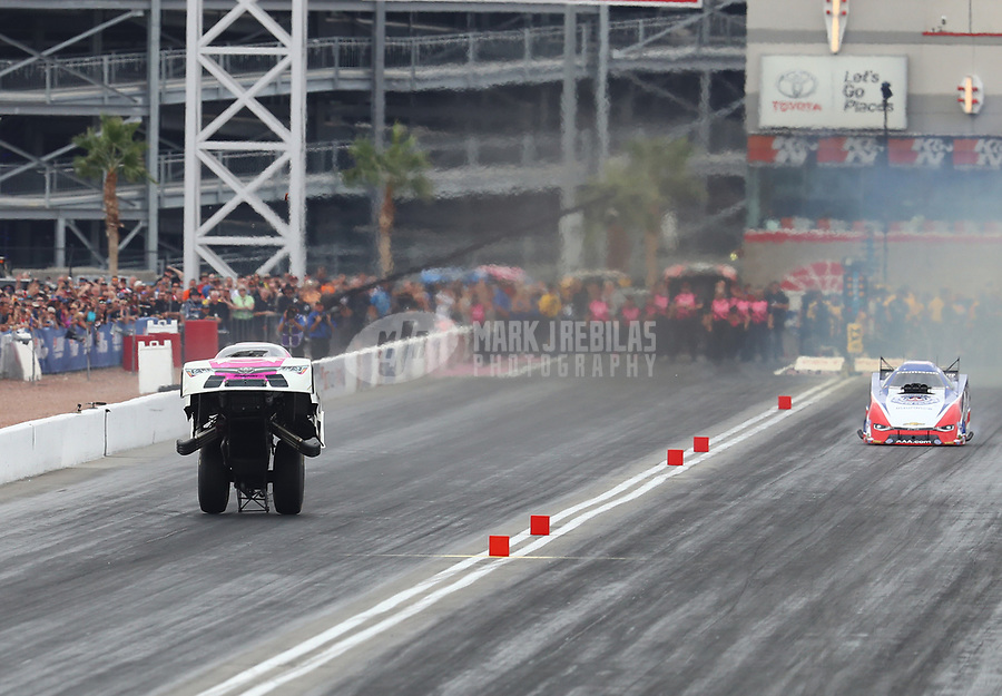 Oct 30, 2016; Las Vegas, NV, USA; NHRA funny car driver Cruz Pedregon (left) does a wheelstand as he wins his round one race against Robert Hight during the Toyota Nationals at The Strip at Las Vegas Motor Speedway. Mandatory Credit: Mark J. Rebilas-USA TODAY Sports
