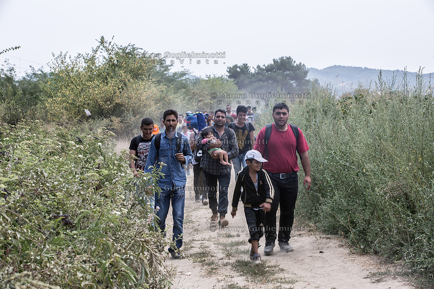 Migranti in marcia nei campi, uno tiene in braccio un neonato Migrants marching in the fields , one is holding a baby