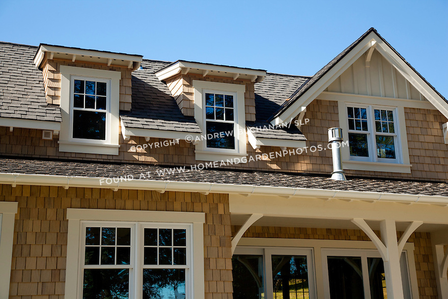 Dormers create more space and allow full windows in the second floor of a waterfront guesthouse.