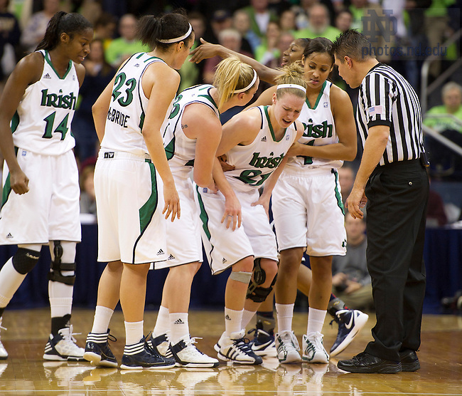 January 7, 2012; Notre Dame Fighting Irish grimaces in pain as teammates come to her aid in the last seconds of the game against the  Connecticut Huskies at the Purcell Pavilion. Notre Dame won 75 to 67 in overtime. Photo by Barbara Johnston/University of Notre Dame