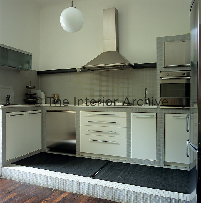 This semi open-plan kitchen has been designed in off white and masculine grey with a raised mosaic tiled floor separating it from the hardwood floor of the living area