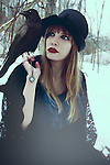 Photograph of a caucasian young woman with blonde hair and red lipstick holding a necklace in her left hand with a clock face on it. She is wearing vintage clothing and sitting in a woodlands area with a black crow perched on her right shoulder. TThe place looks very cold and is covered in snow.
