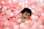 A plays in a bath of pink and white plastic balls during  the opening of Hello Kitty's Kawaii (Cute) Paradise, a Hello Kitty theme store, in Tokyo, Japan on Thursday 21 October  2010. .Photographer: Robert Gilhooly