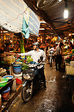 VIETNAM, Hanoi, Chau Long Market, a man rides him moped through the market and stops to buy some potatoes