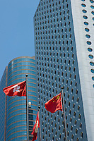 Chinese flags flying in front of modern skyscrapers, Hong Kong Island, Hong Kong, China.