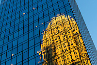 The Bank of America tower reflects in the glass of a nearby building.
