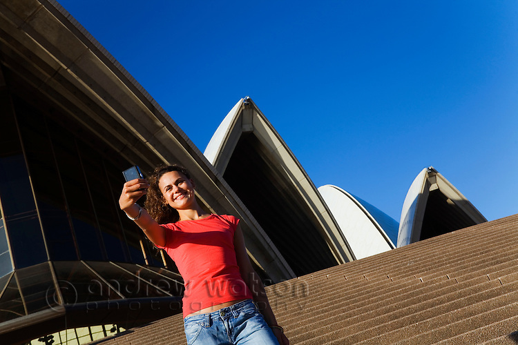 A woman takes a self portrait on the steps of the Opera House.  Sydney, New South Wales, AUSTRALIA.
