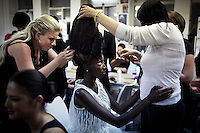 JOHANNESBURG, SOUTH AFRICA - FEBRUARY 19: Huguette Marara a model from Rwanda, is fitted with a hair piece before a show with the designer David Tlale, at his studios at the Joburg Fashion Week on February 19, 2011, in Johannesburg, South Africa. David Tlale, is an award winning designer and one of South Africa's finest designers, dressing celebrities and others in couture with elegance and high quality material. He held his show at the Mandela Bridge in downtown Johannesburg. A logistical nightmare, the bridge was closed and turned into a catwalk at midnight with hundreds of people watching the show. 92 models, one for each of Nelson Mandela's years walked the 285 meter bridge, maybe the longest catwalk in the world. South African top designers with showed their 2011 Autumn & Winter collections during the 5 day event. (Photo by Per-Anders Pettersson