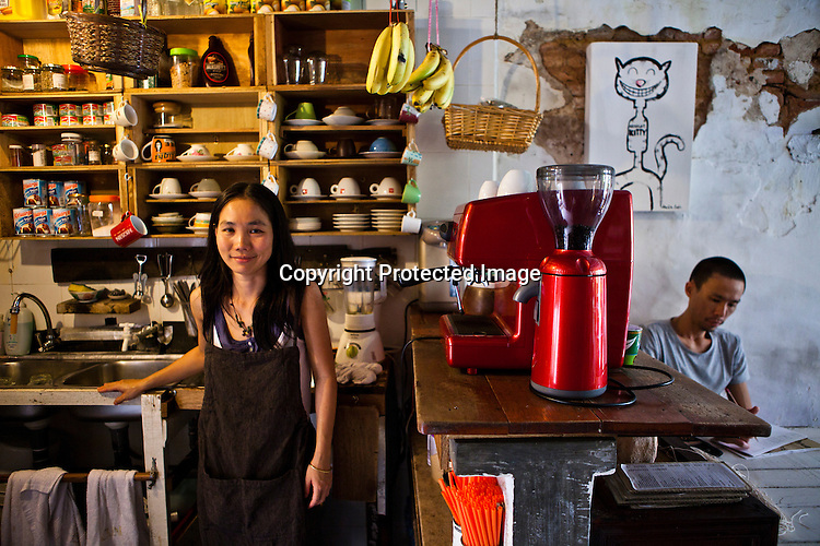 37 year old Khor Gaik Ee poses for a portrait while her partner, Loh Choon Kueng (38) sketches in the background at the Amelie Cafe in old part of capital Georgetown of Penang, Malaysia. Photo: Sanjit Das/Panos