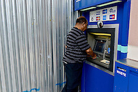 MIRAMAR, FL - OCTOBER 06: Banks consumer getting cash out of the ATM machine while the bank hurricane shutters is install before the Hurricane Matthew approaches the area on October 6, 2016 in Miramar, Florida. The hurricane is expected to make landfall sometime this evening or early in the morning as a possible category 4 storm.Credit: MPI10 / MediaPunch