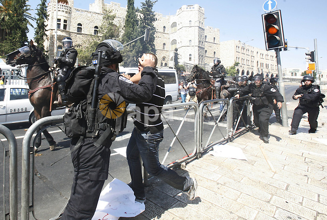 Israeli policeman clashes with a Palestinian protester during a demonstration against the controversial film 'Innocence of Muslims' in front of al-Aqsa Mosqe in Jerusalem, on September 14, 2012. The controversial low budget film reportedly made by an Israeli-American which portrays Muslims as immoral and gratuitous, sparked fury in Libya, where four Americans including the ambassador were killed on Tuesday when a mob attacked the US consulate in Benghazi, and has led to protests outside US missions in Morocco, Sudan, Egypt, Tunisia and Yemen. Photo by Mahfouz Abu Turk