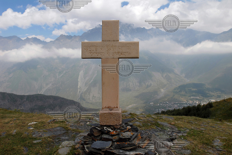 Cross on a hill outside the 14th Century Tsminda Sameba Church, a symbol of Georgia, in the Kazbegi mountains.