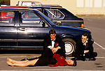 MEN WATCH OVER FEMALE COMPANION, LYING ASLEEP IN THE CARPARK AT MAY BALL, ROYAL AGRICULTURAL COLLEGE. CIRENCESTER,