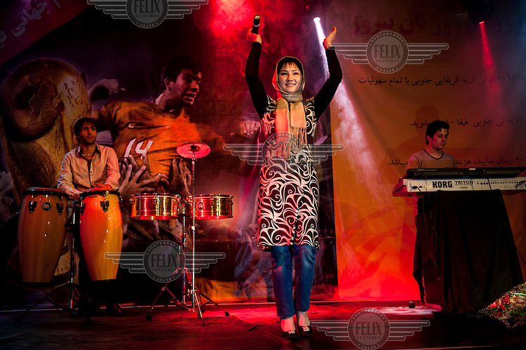 A singer encourages the crowd at a concert in Kabul. /Felix Features
