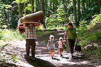 A family carries camping gear and a canoe the quarter mile from the parking lot to the trail head at Craig Lake State Park near Michigamme Michigan.