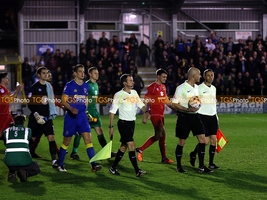 Referee Roger East leads out the two teams during AFC Wimbledon vs MK Dons, Sky Bet EFL League 1 Football at the Cherry Red Records Stadium on 14th March 2017