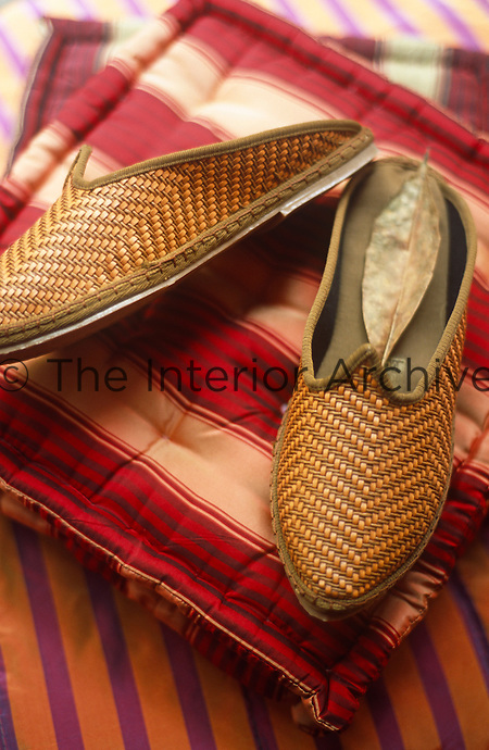 A pair of woven slippers rest on a pile of square striped cushions