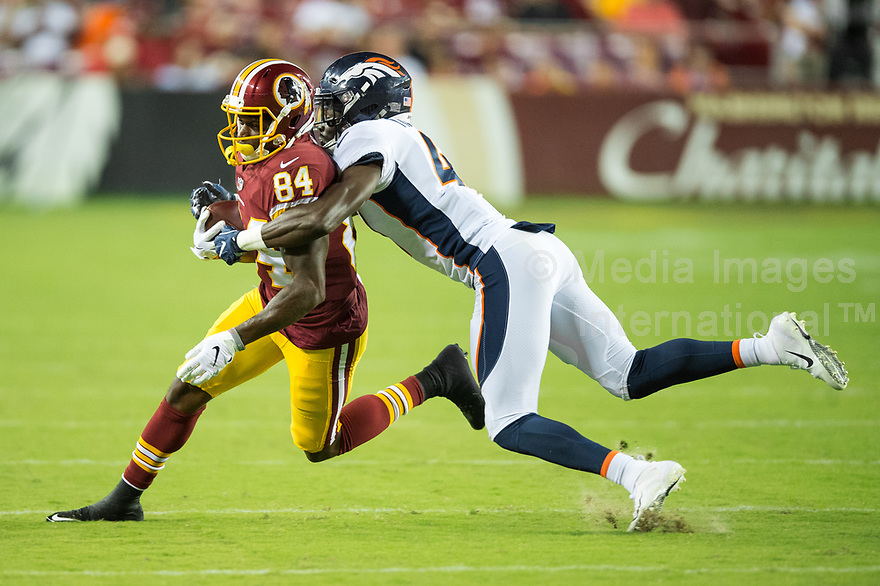 Landover, MD - August 24, 2018: Washington Redskins wide receiver Darvin Kidsy (84) is tackled by Denver Broncos cornerback Isaac Yiadom (41) during preseason game between the Denver Broncos and Washington Redskins at FedEx Field in Landover, MD. The Broncos defeat the Redskins 29-17. (Photo by Phillip Peters/Media Images International)