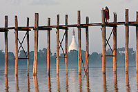 Myanmar, Burma, Mandalay, Amarapura.  Buddhist Monk on the U Bein Bridge at the end of the day.  The teak footbridge is 200 years old, and 1300 yards long.