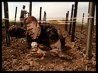 Tustin Marine Corps Air Station--With drink in hand Sargeant Steve Rhoads makes his way through the low crawl pit part of the 6.2 mile course for the 15th annual Volkslauf Mud Run.