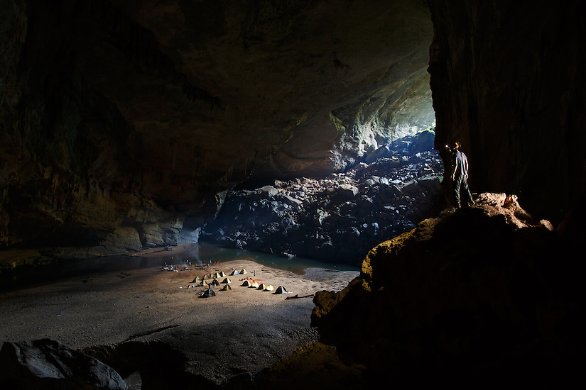 A caver overlooks camp in Hang En, Phong Nha Ke Bang, Vietnam