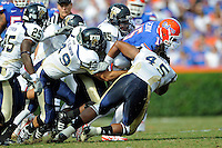 21 November 2009:  FIU defensive tackle Justin West (95), linebacker Tyler Clawson (49) and linebacker Aaron Davis (45) combine to tackle Florida quarterback Tim Tebow in the first quarter as the University of Florida Gators defeated the FIU Golden Panthers, 62-3, at Ben Hill Griffin Stadium in Gainesville, Florida.