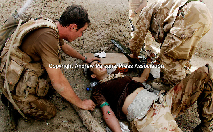 A Soldier from the Worcester and Sherwood Foresters regiment (left) looks on as medics work on the injuried soldier who got shot by the Taliban during an ambush inside the Green Zone in Helmand Provence, Southern Afghanistan, PRESS ASSOCIATION Photo. Picture date:Tuesday 14th August   , 2007. Photo credit should read: Andrew Parsons/PA.