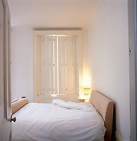 View into the small bedroom with original wooden shutters covering the window