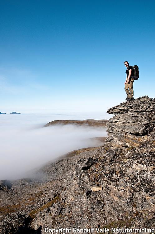 Mann ser at lavereliggende deler av Sørøya dekkes av havskodde. ----- Man sees that lover parts of Sørøya are covered in mist.