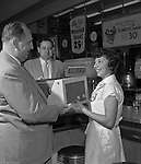 Pittsburgh PA:  A Thrift Drug waitress accepting a new phonograph from Hamburg Brothers after winning their weekly radio contest.<br />